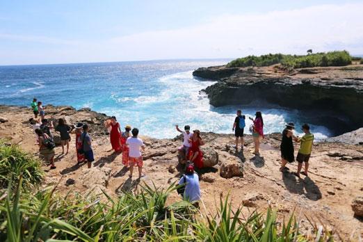 レンボンガン島のデビルティアーズを観光する人々