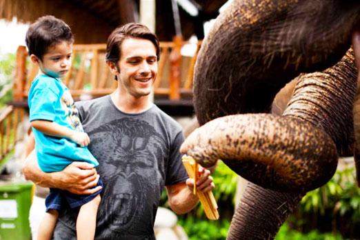 象にエサをあげるお父さんと子供