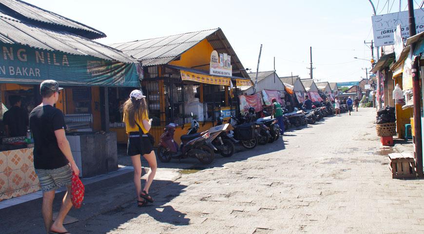 ジンバランの魚市場の裏手の通りを歩くオーストラリア人のカップル