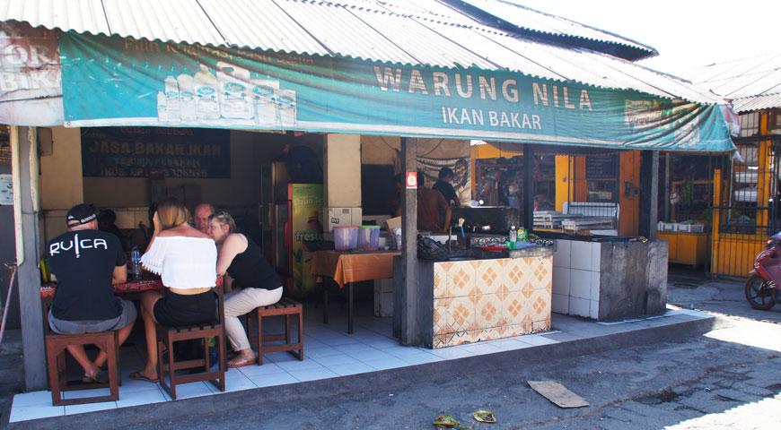 ジンバランの魚市場横のワルンで食事をする欧米人の家族