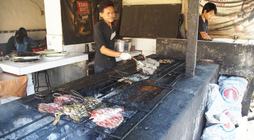 焼き場で魚介類の配置を変えるスタッフA