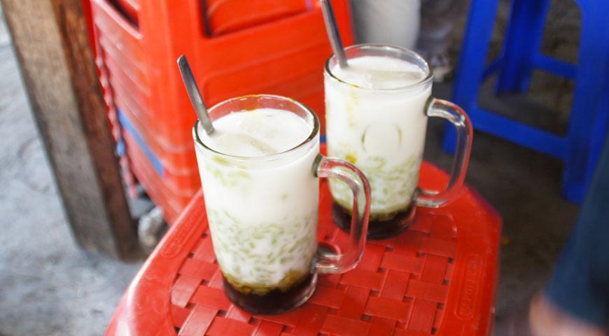 白い液体と緑色のゼリーと底にたまる黒のシロップが入ったグラス