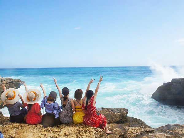 レンボンガン島デビルティアーズで海に向かってピースをする女性グループ