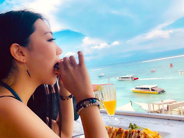ルーフトップバーで食事をする女性とレンボンガンの快晴の空と海