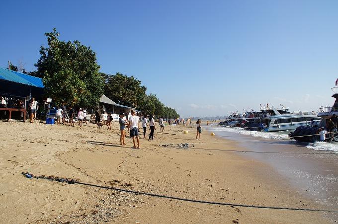 晴れた日にサヌールビーチへ降り立つ観光客と沢山の高速船