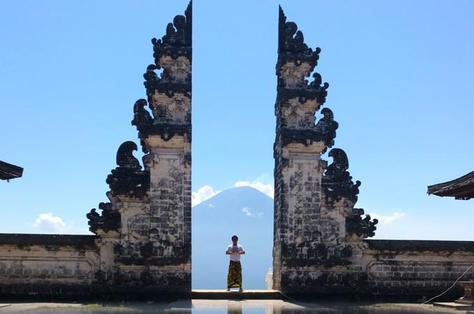 ランプヤン寺院の割れ門でアグン山を背に記念撮影をする男性