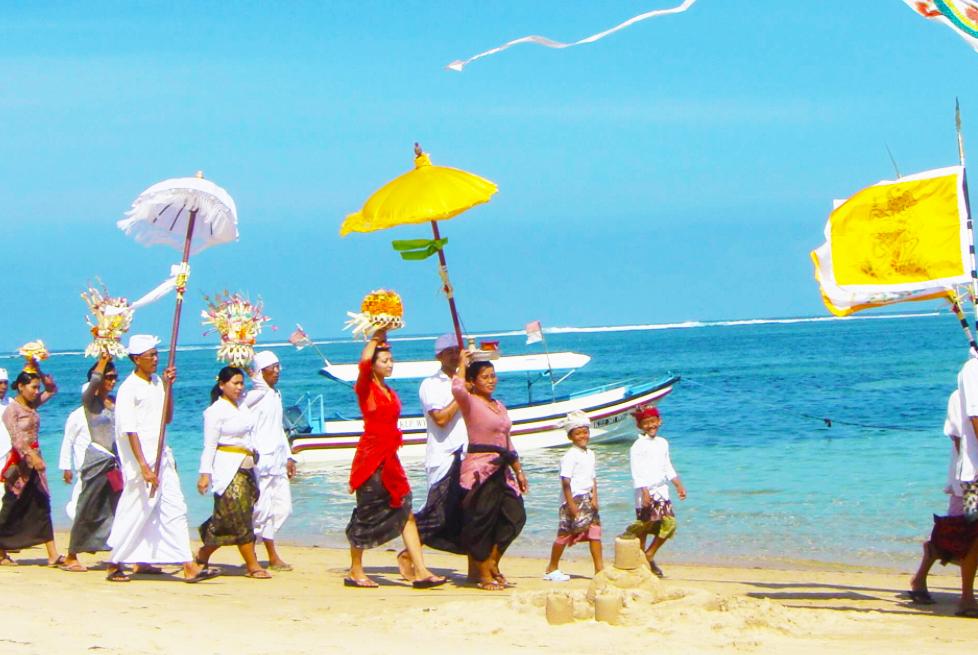 きれいな海岸沿いを祭事のために行進するバリニーズたち